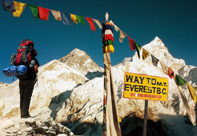 Evening View of Everest with Hiker and Buddhist Prayer Flags from Kala Patthar